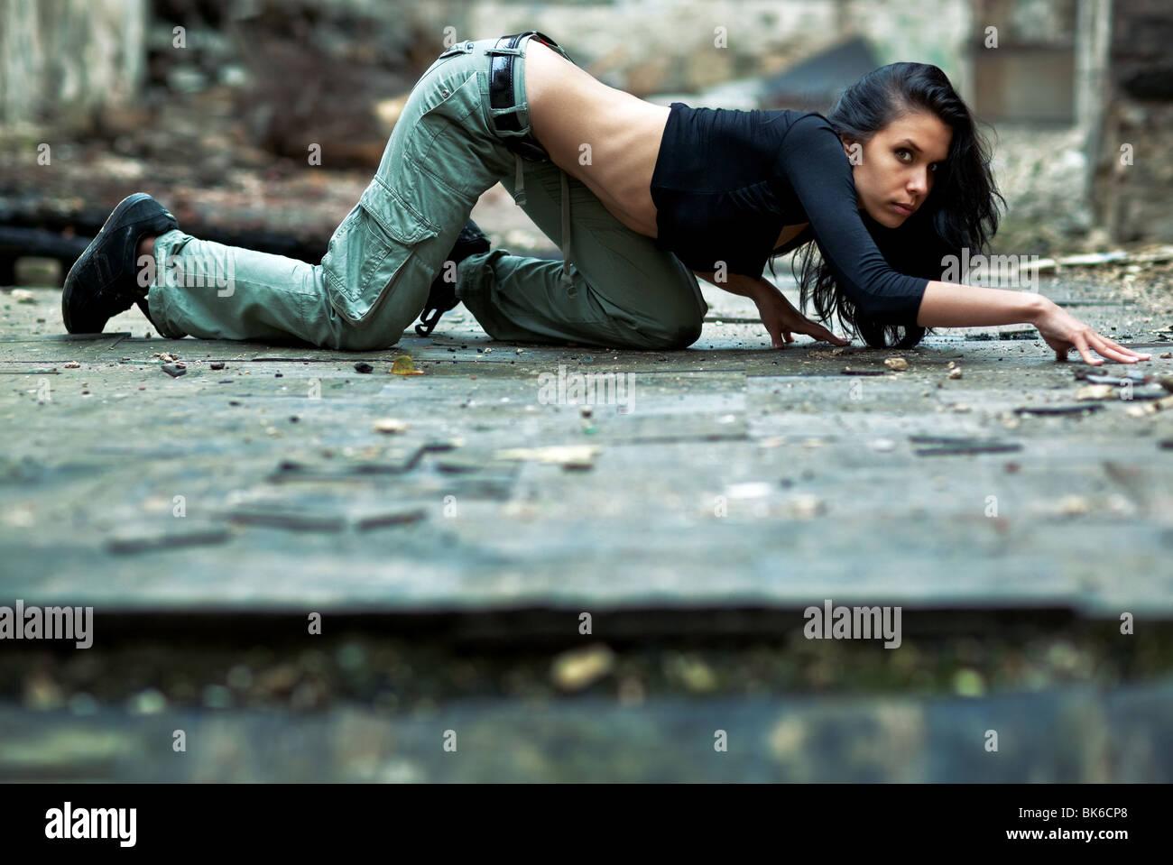 Junge Frau in einem verfallenen Gebäude. Heimlich kriechen auf dem Boden. Stockbild