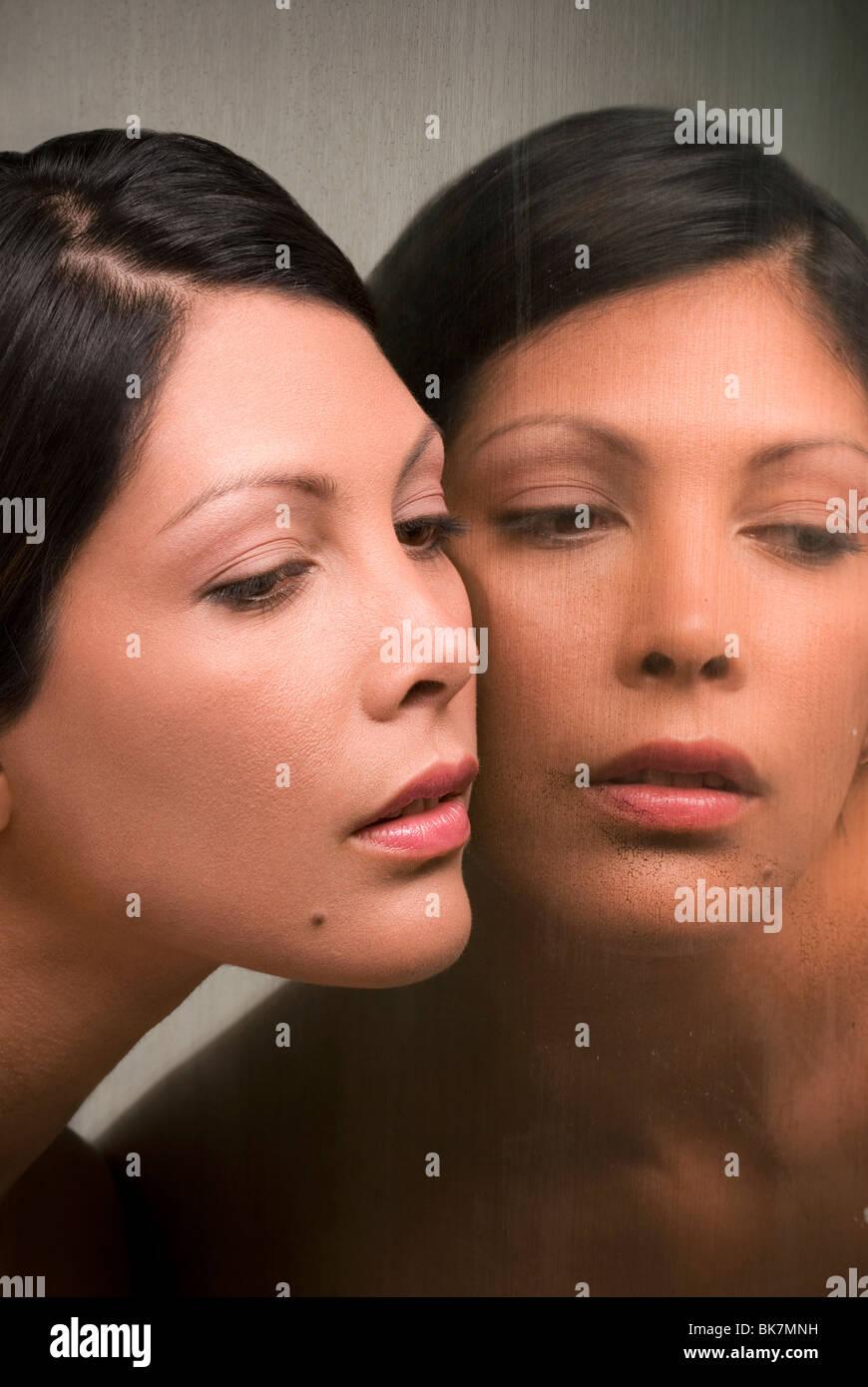 Junge Hispanic Frau und ihr Spiegelbild Stockbild
