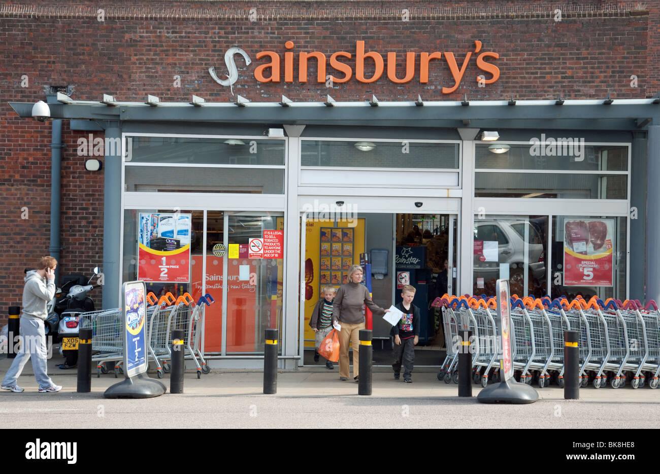 Käufer außerhalb eines Sainsburys Ladens mit einem gebrochenen Schild Stockbild