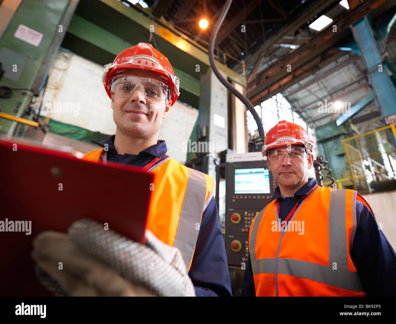 Stahl-Ingenieure im Werk mit Zwischenablage Stockfoto