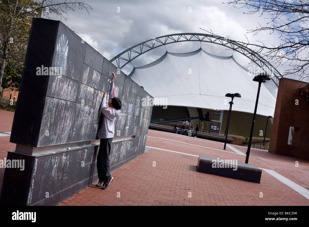 Junge stützt sich auf Community-Tafel und Podium, Downtown Mall, Pavillon hinter, Charlottesville, Virginia Stockbild