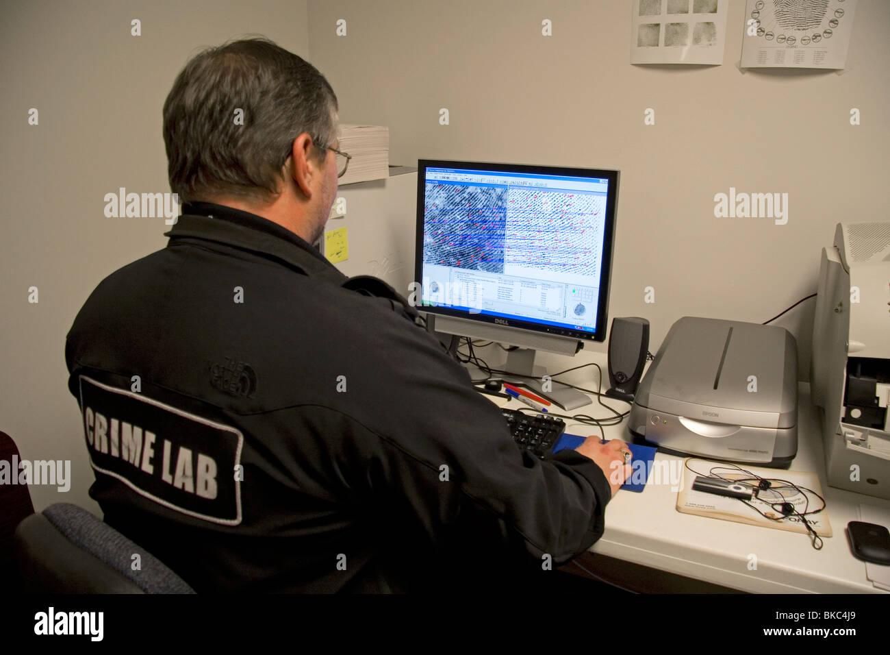 Fingerabdruck-Analyst mit Hilfe eines Computers, um Fingerabdrücke in einem Verbrechen Labor zu klassifizieren. Stockbild
