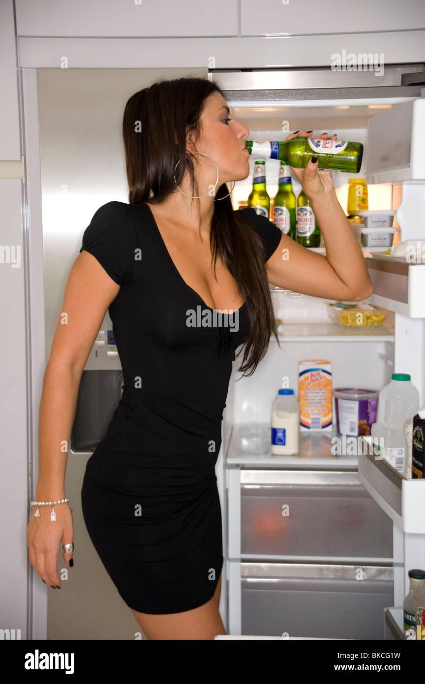 sexy dunkelhaarige Mädchen trinken ein Bier vor einem Kühlschrank ...