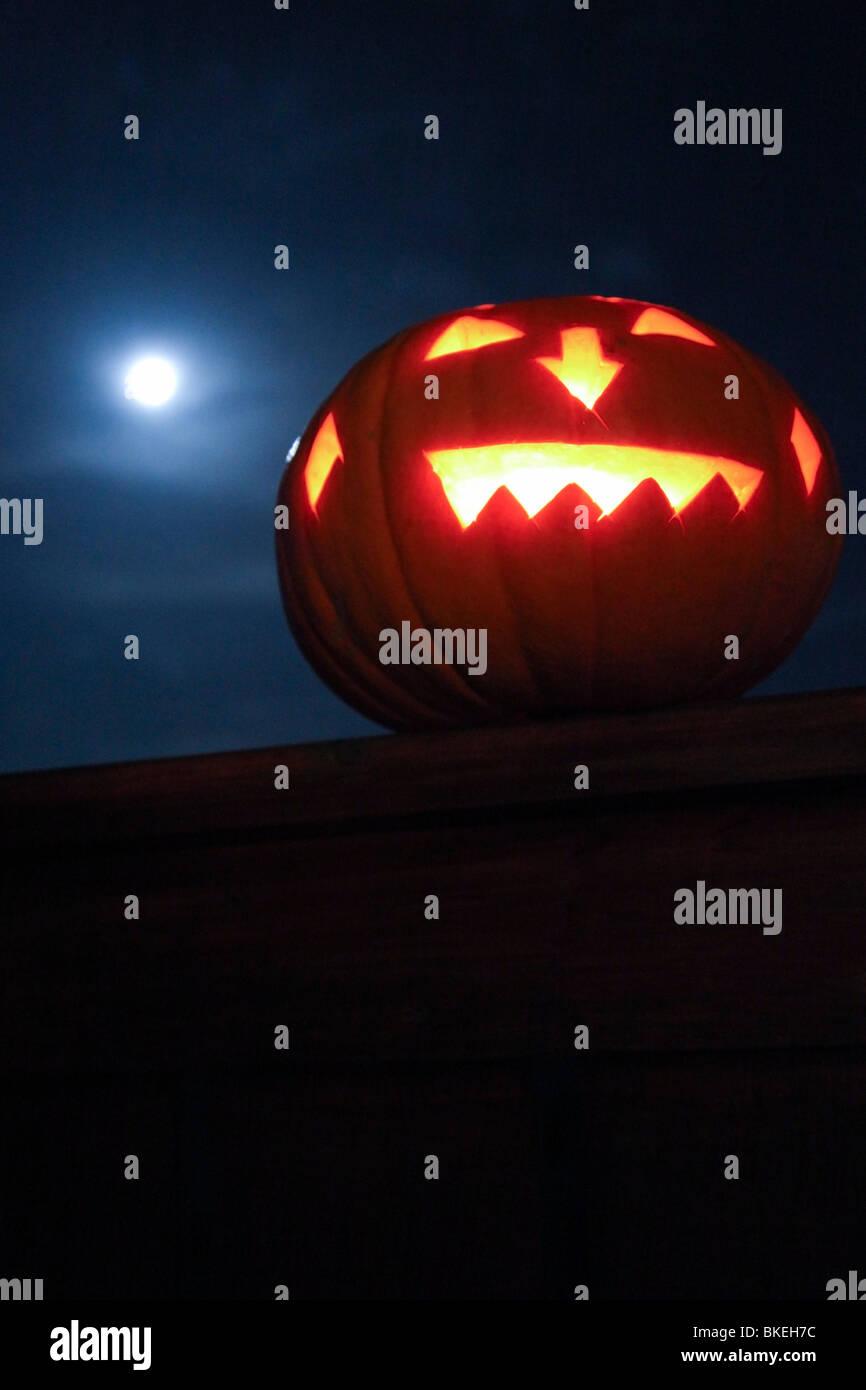 Eine beleuchtete Jack-O-Laterne auf dem Zaun in der Nacht Stockbild