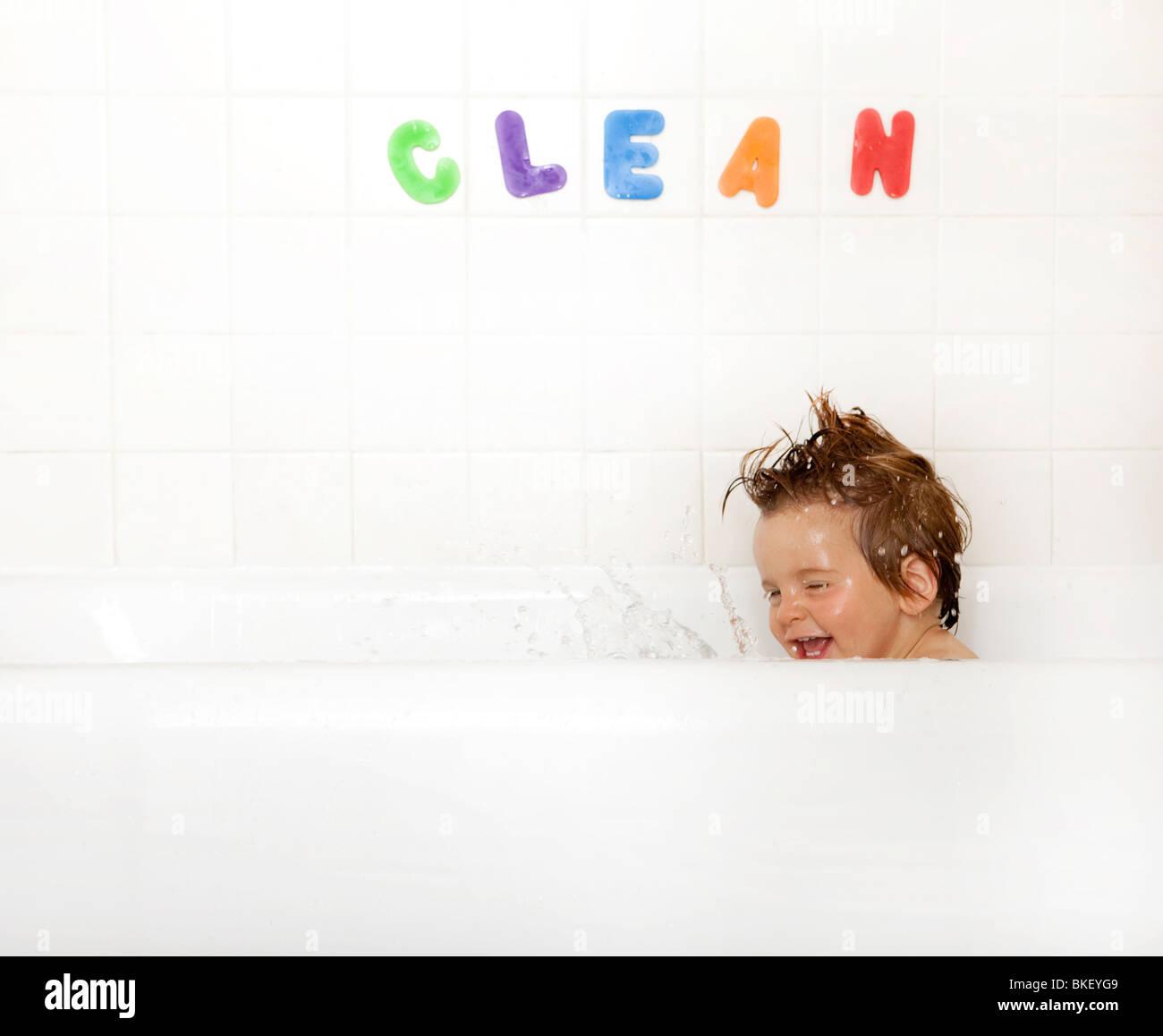 Boy spritzt in Badewanne Stockbild