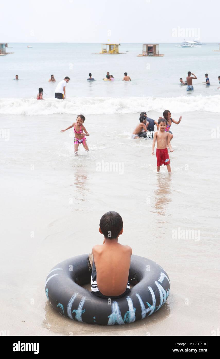 Junge auf gestrandeten Gummiring beobachten Kinder Matabungkay Strand spielen; Batangas; SüdLuzon; Philippinen Stockbild