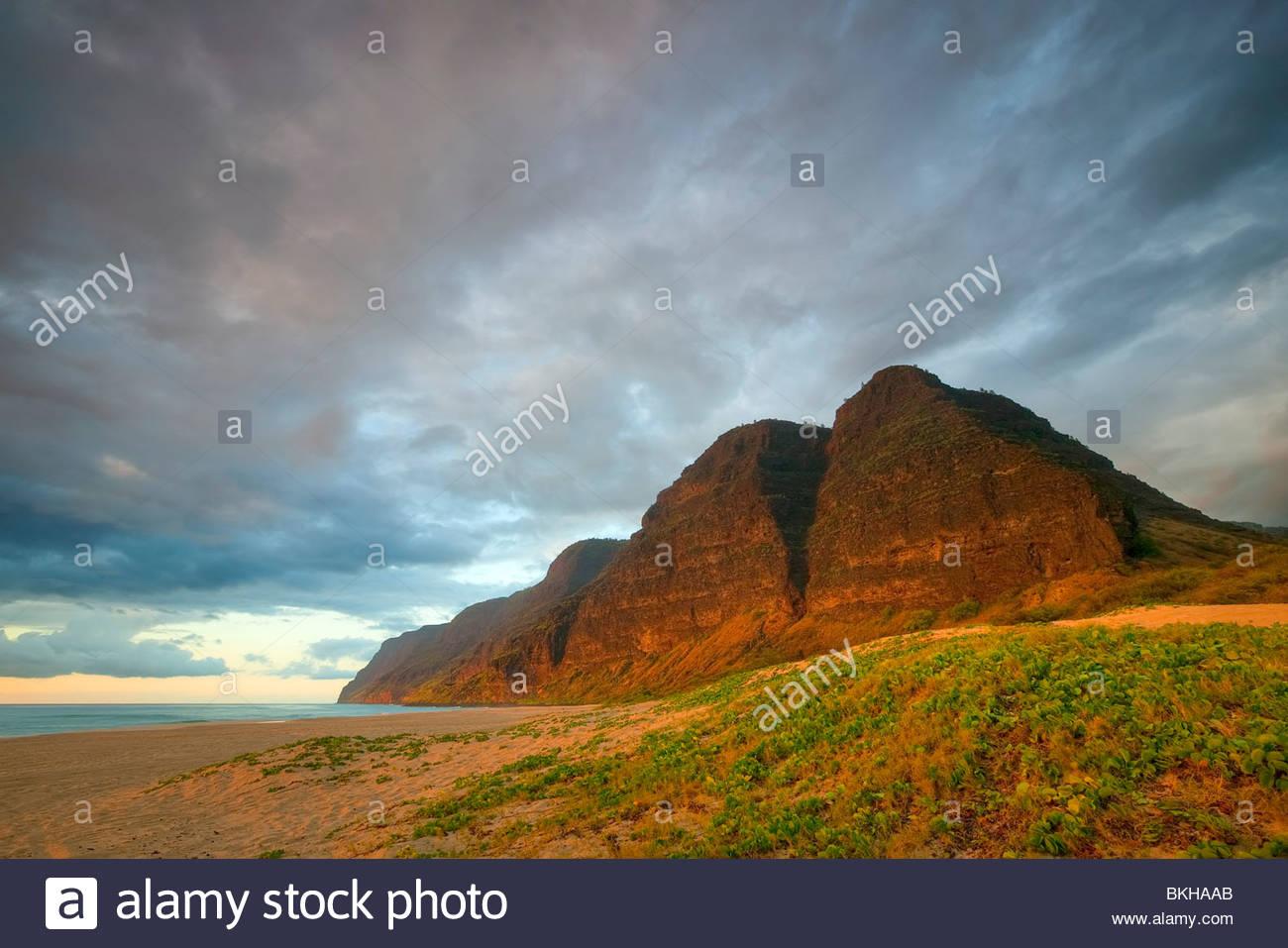 Die untergehende Sonne leuchtet mehrere hohe Berge über Barking Sands Beach im Polihale State Park, Kauai, Stockbild