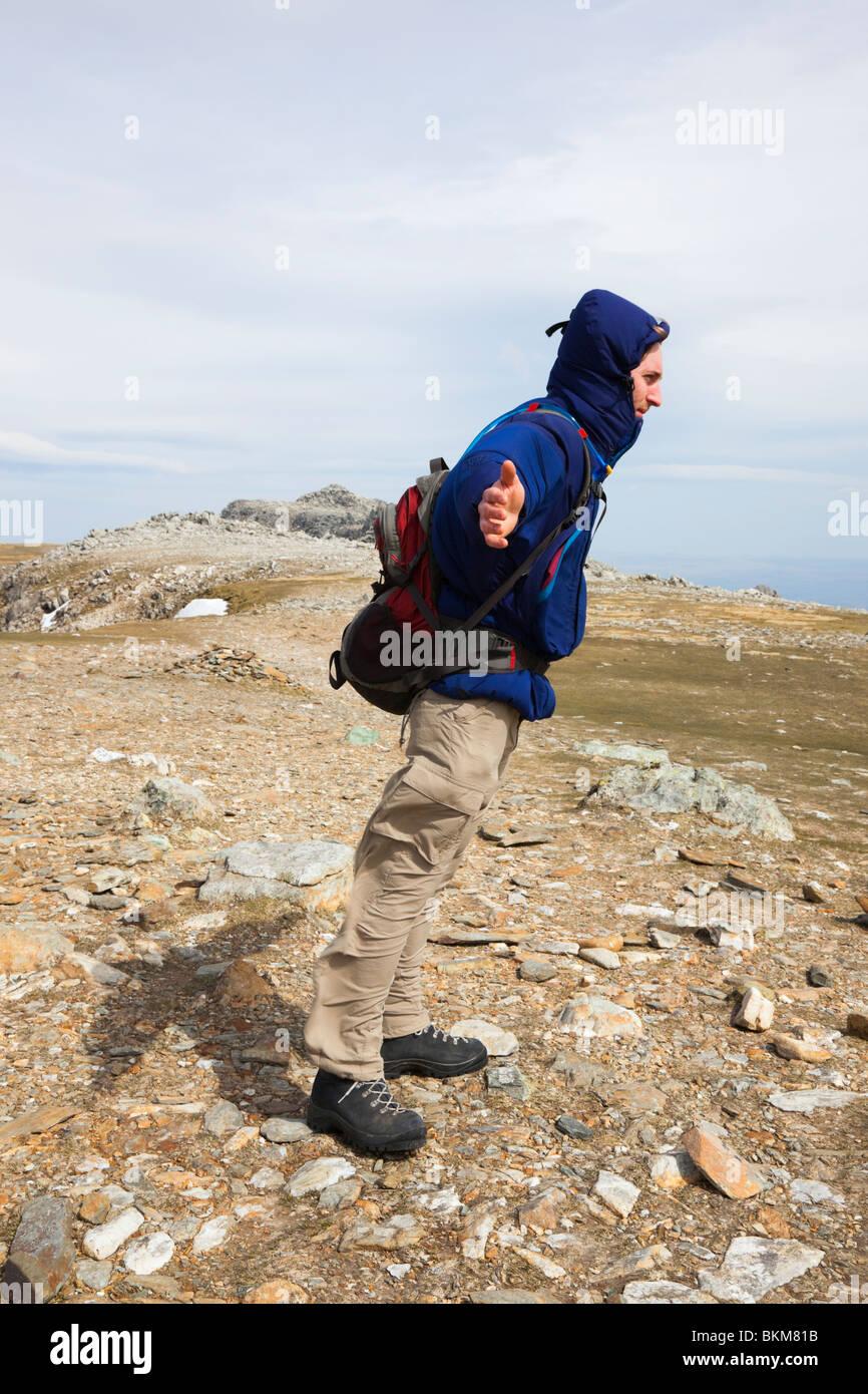 Man lehnt sich dem Wind an einem sehr windigen Tag auf exponierte Berggipfel der Glyder Fawr im Snowdonia National Stockbild
