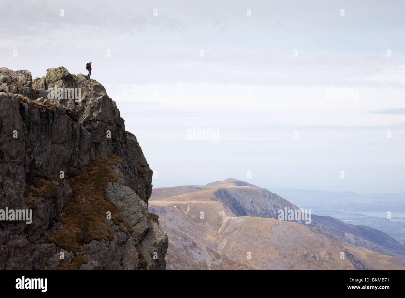 Mann steht allein auf einem schroffen Berggipfel mit Blick über. Glyder Fawr Ogwen Snowdonia National Park Stockbild