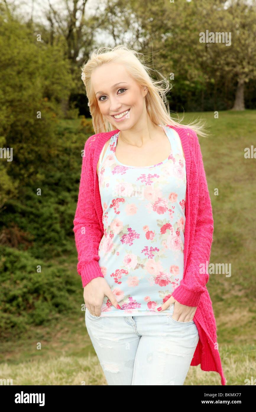 Drei Viertel Länge Porträt eine hübsche junge blonde Frau auf Kamera zu Lächeln Stockbild