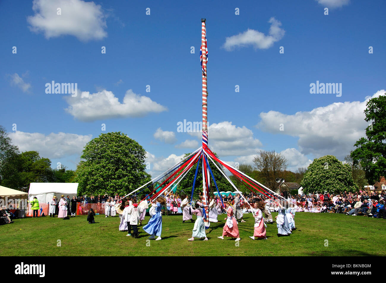 Kinder tanzen um den Maibaum, The Ickwell May Day Festival, Ickwell Green, Ickwell, Bedfordshire, England, Vereinigtes Stockbild