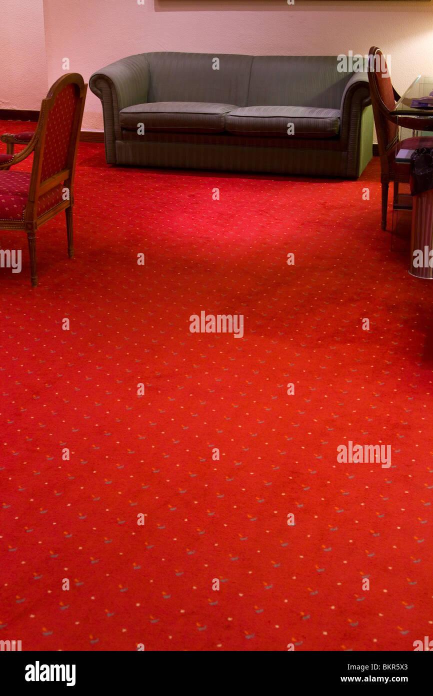 Spärlich Möbel und einen hellen roten Teppich in einem Budget-Hotel-Lobby. Stockbild