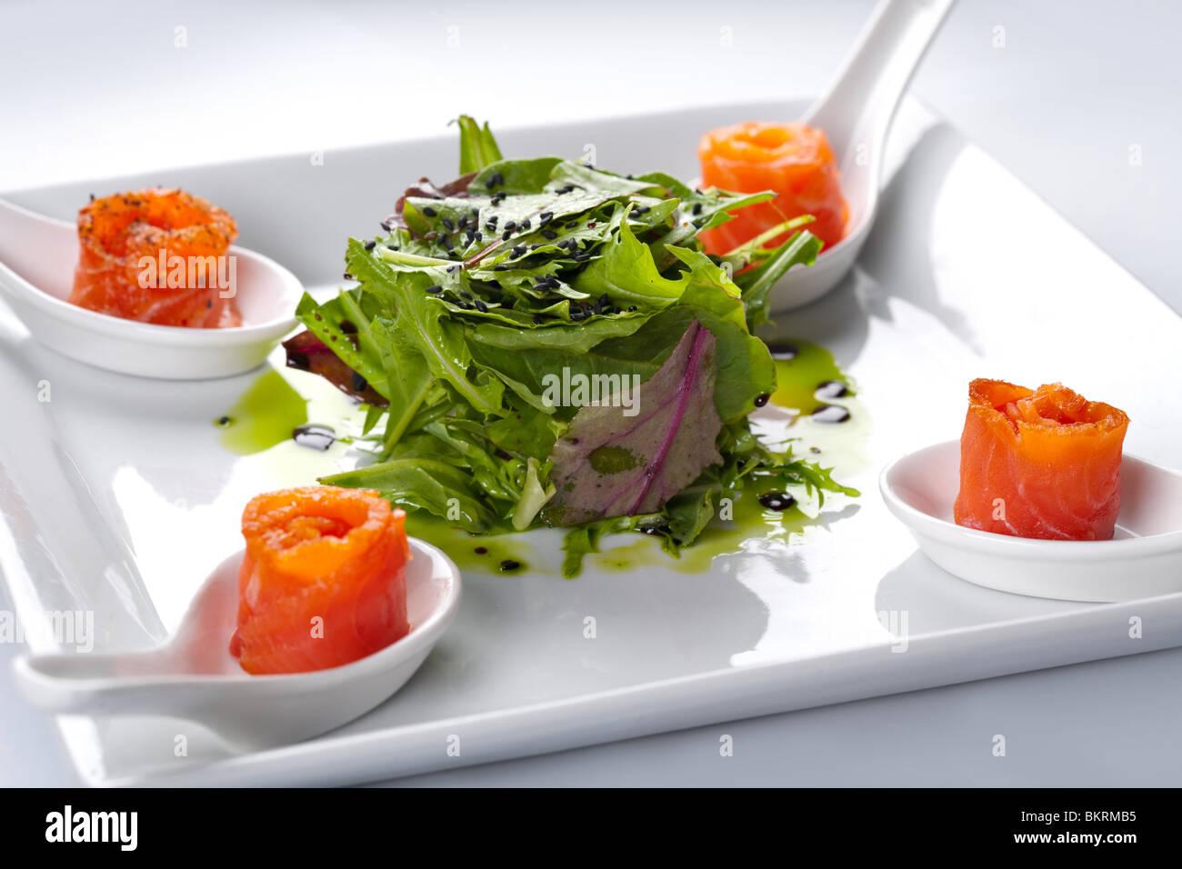 Lachs in einem weißen Teller. In der Mitte Rucola Salat. Stockfoto
