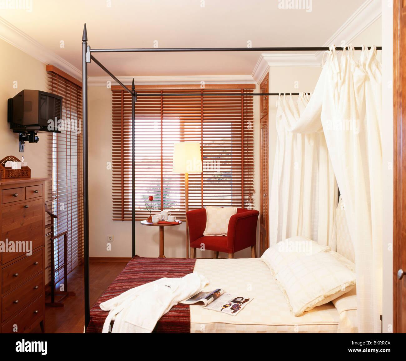 Weiße Vorhänge Auf Einfache Metall Himmelbett Im Schlafzimmer Mit  Lattenrost Aus Holz Rollo Am Fenster Und Fernseher An Der Wand Montiert