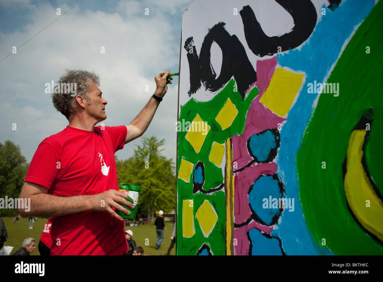 Feier der Welt 'Fair Trade'-Tag, mit man Gemälde an der Wand, auf dem Rasen von La Villette Park, zum Stockbild