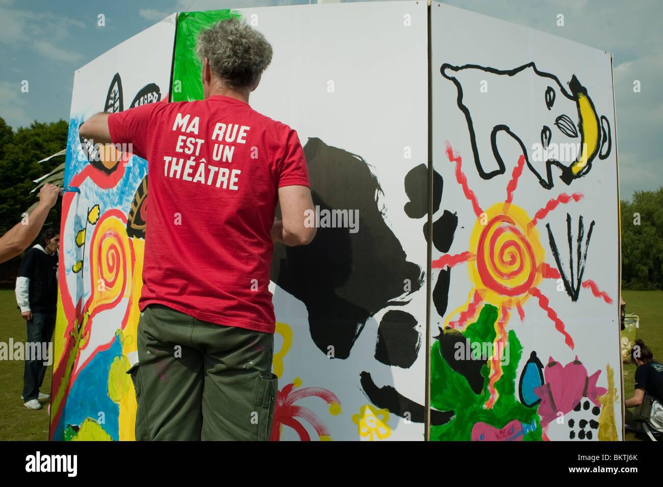 """""""Fairer Handel"""" Welttag, Mann Malerei Wand auf Rasen von La Villette Park Kauf fairer Handel fördern Stockbild"""