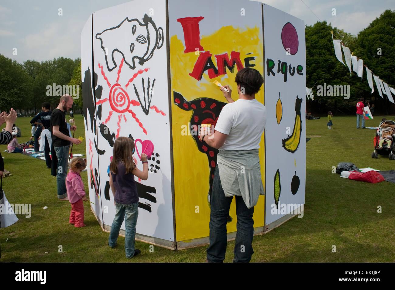 Feier der Welt 'Fair Trade'-Tag, mit Menschen Gemälde an der Wand, auf dem Rasen von La Villette Park, Stockbild