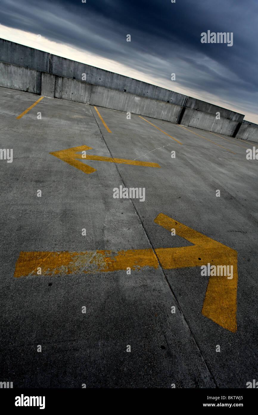 Zwei gelbe Richtungspfeile auf Parkplatz. Stockbild