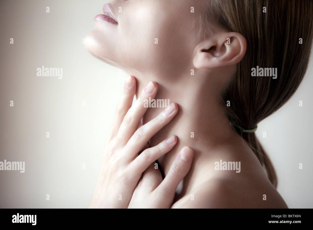 Junge Frau mit den Händen auf Hals, Augen geschlossen Stockbild