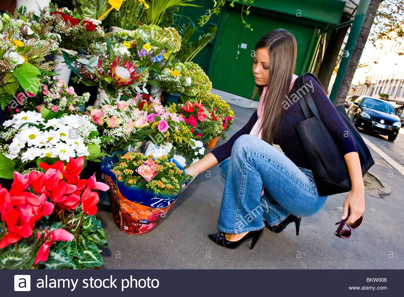 Frau kauft eine Pflanze von dem Floristen Stockbild
