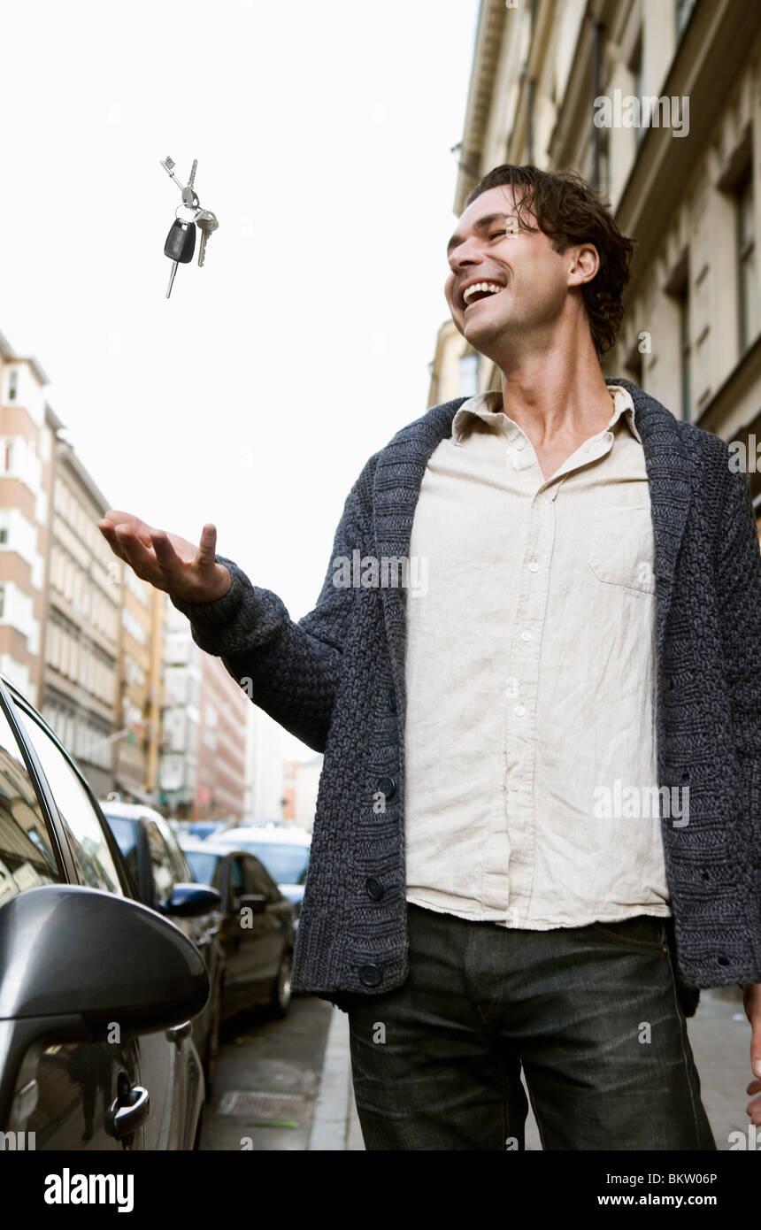 Mann, die Schlüssel in die Luft werfen Stockbild