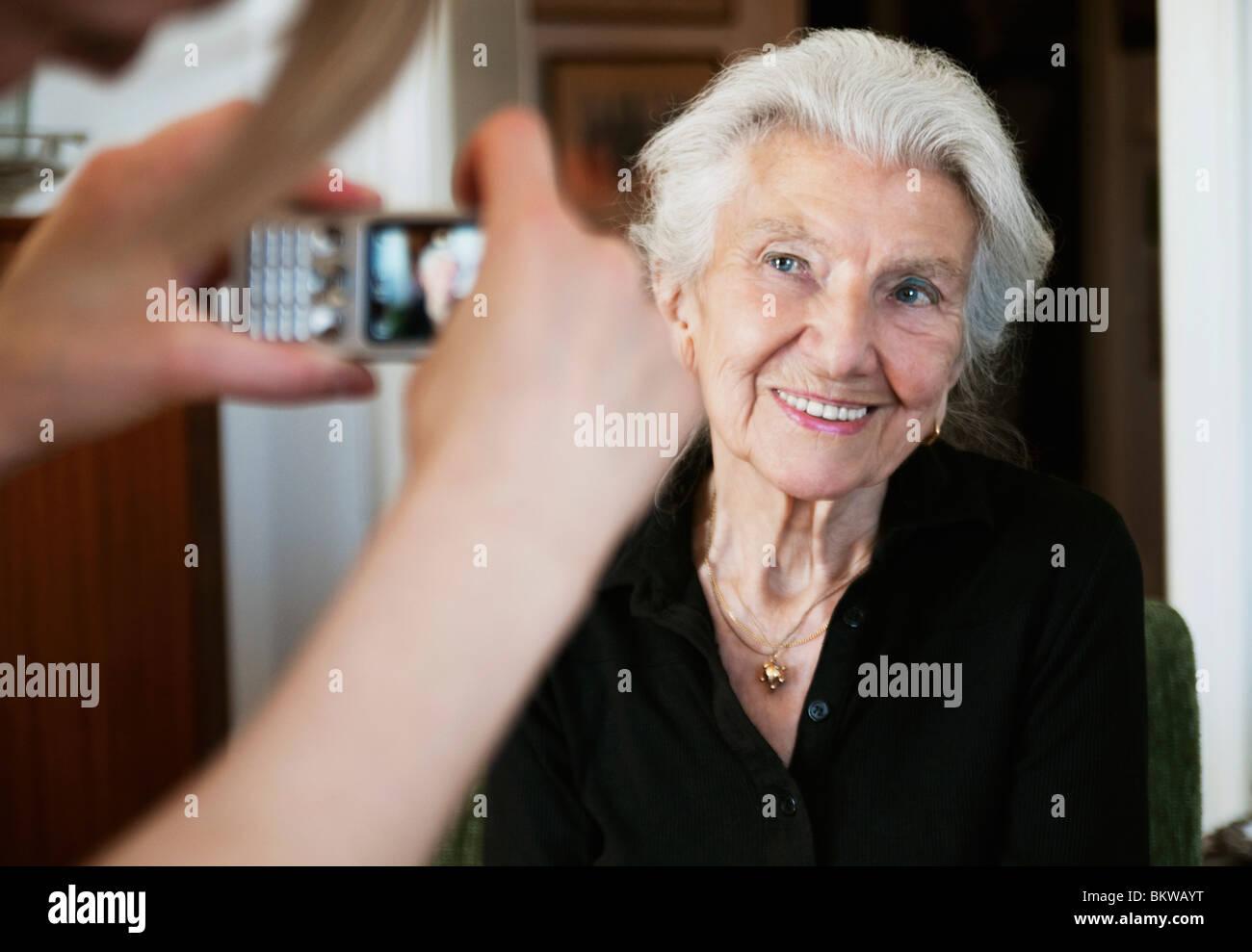 Frau, die Fotos mit Kamera-Handy Stockbild