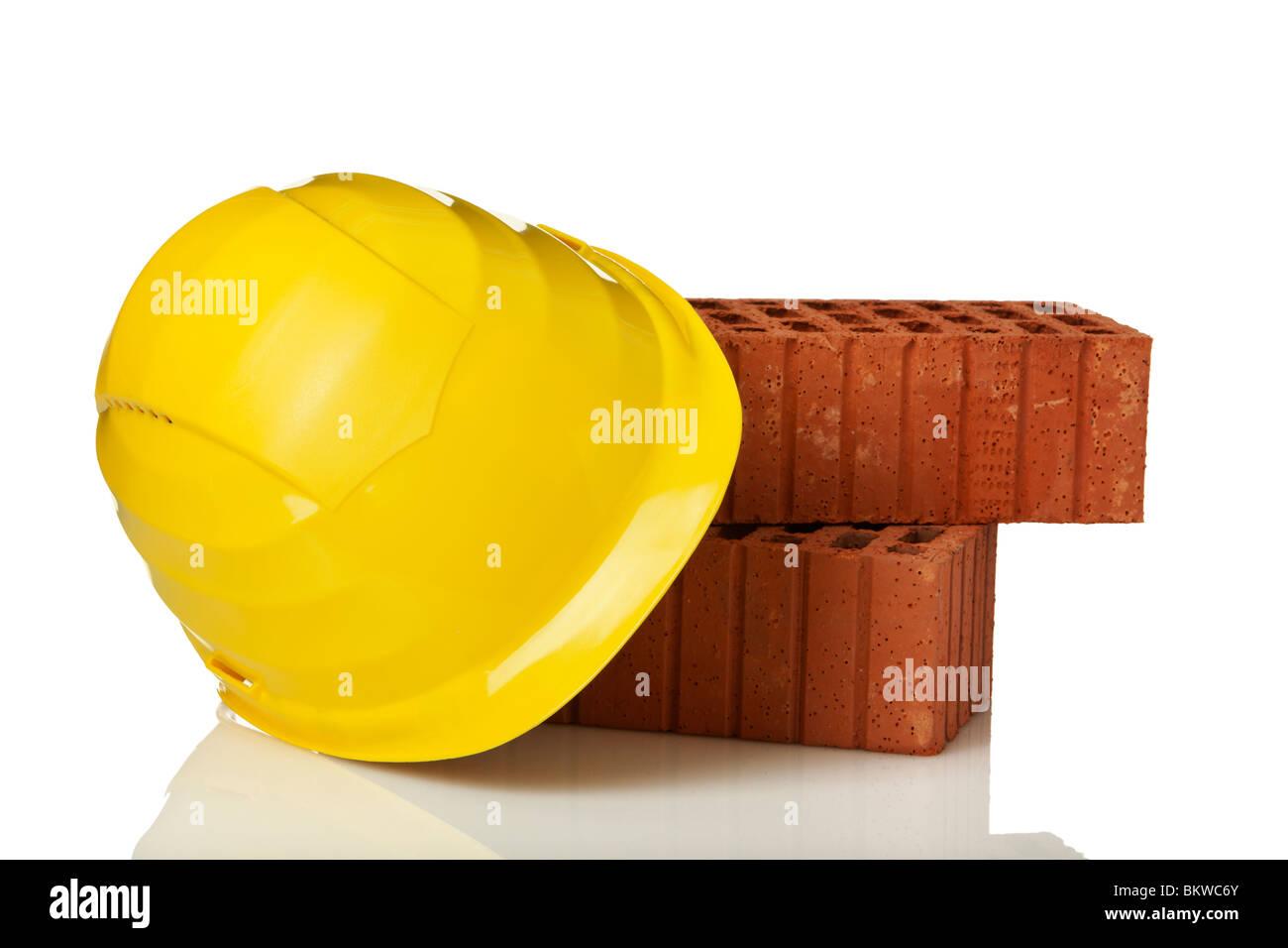 Gelben Bauarbeiterhelm Und Ziegel Auf Weissem Hintergrund Stockfoto