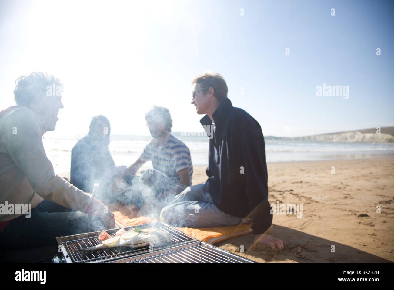 Gruppe von Freunden sitzen um ein Barbecue am Strand Stockfoto
