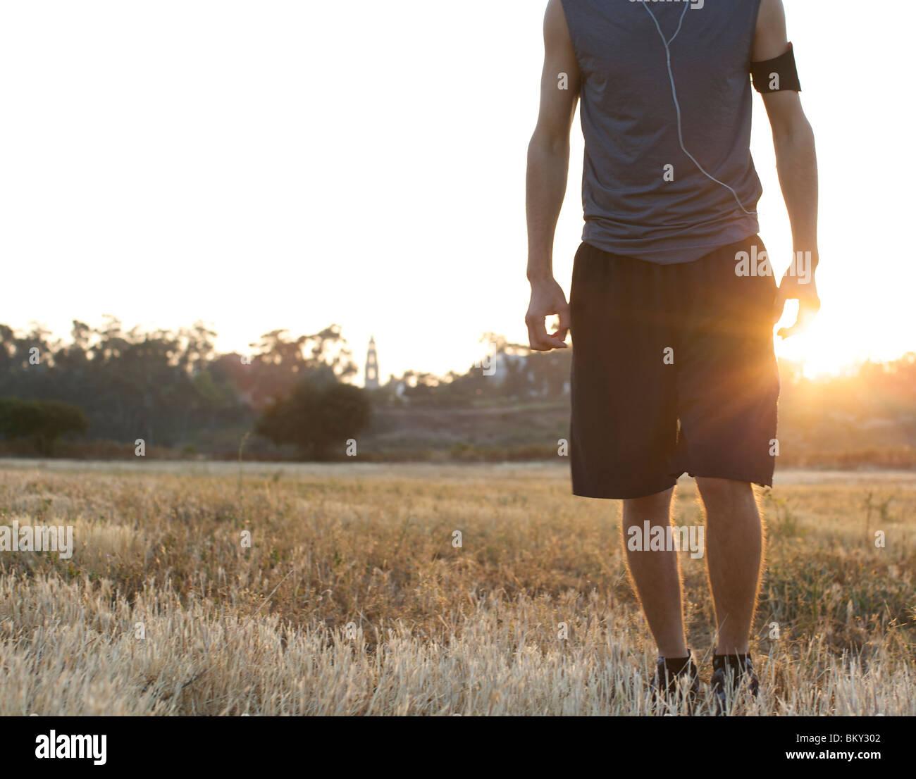 Männliche Läufer bleibt noch für ein Portrait auf einem offenen Feld mit Hintergrundbeleuchtung in Stockbild