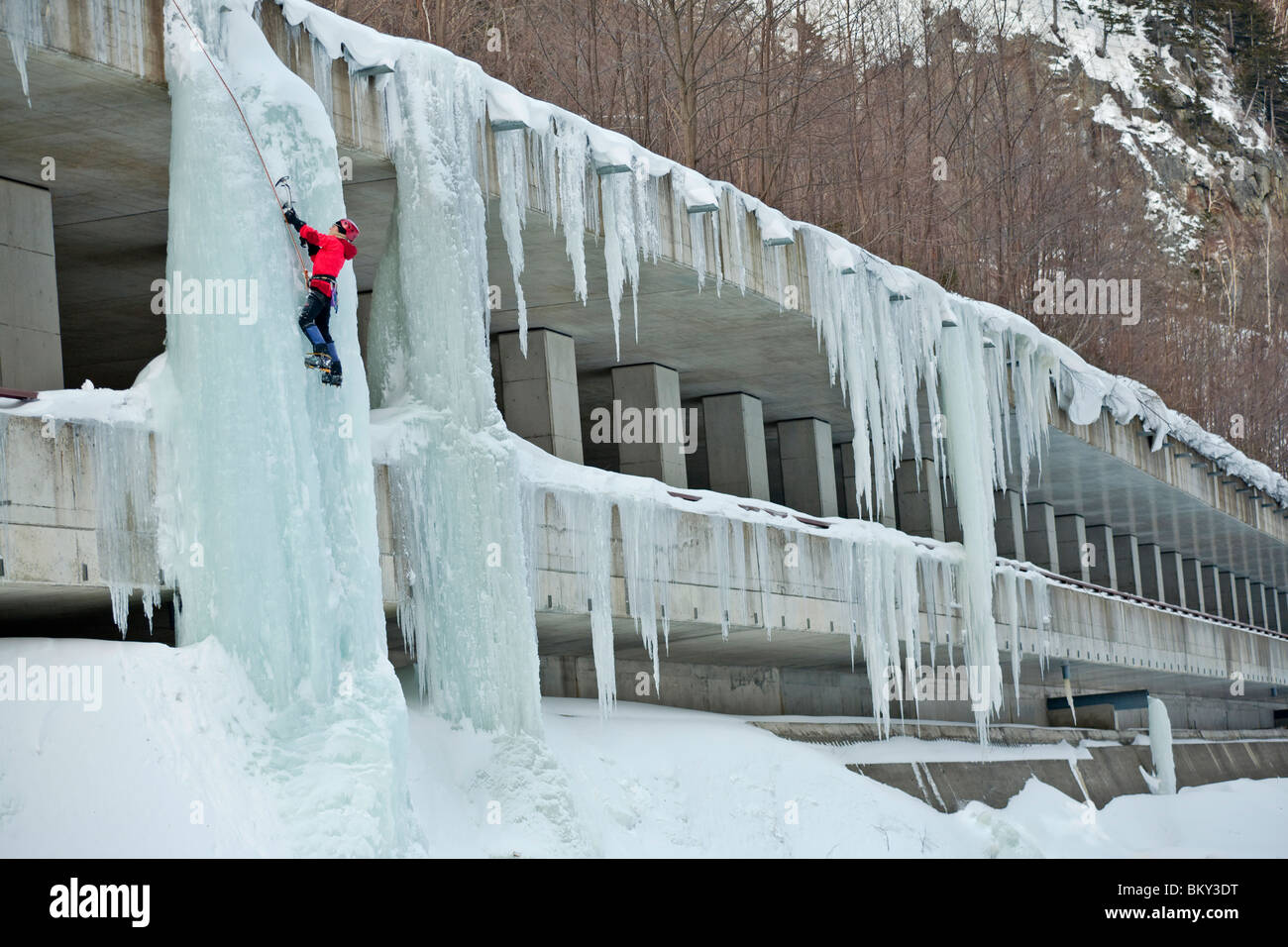 Eine Frau steigt eine Eissäule auf einer Autobahn in Sounkyo Schlucht, Daisetsuzan Nationalpark, Hokkaido, Stockbild