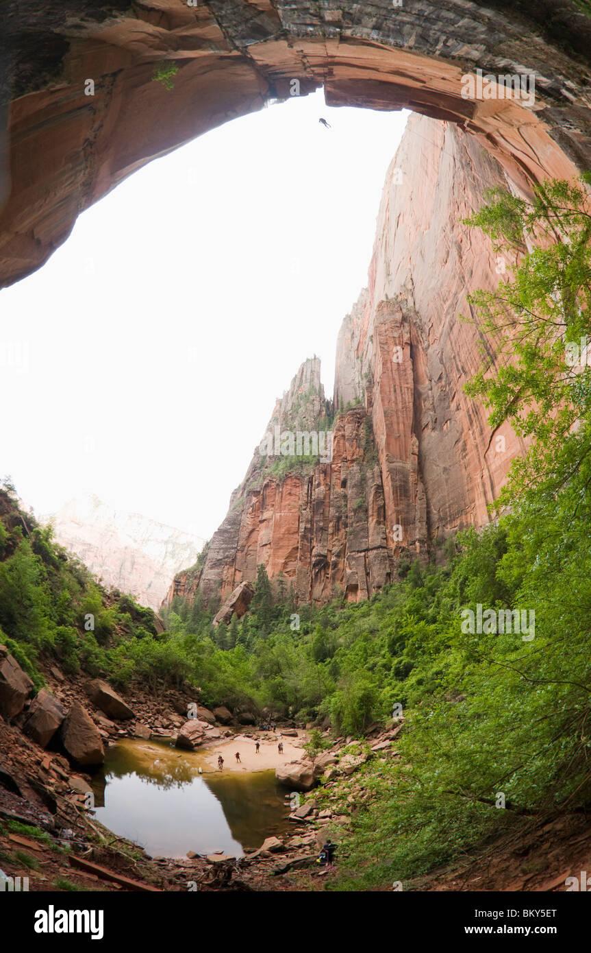 Ein Canyoning-Mann Abschluss eine kostenlose Abseilen am Ende des Heaps Canyon, Zion National Park, Springdale, Stockbild