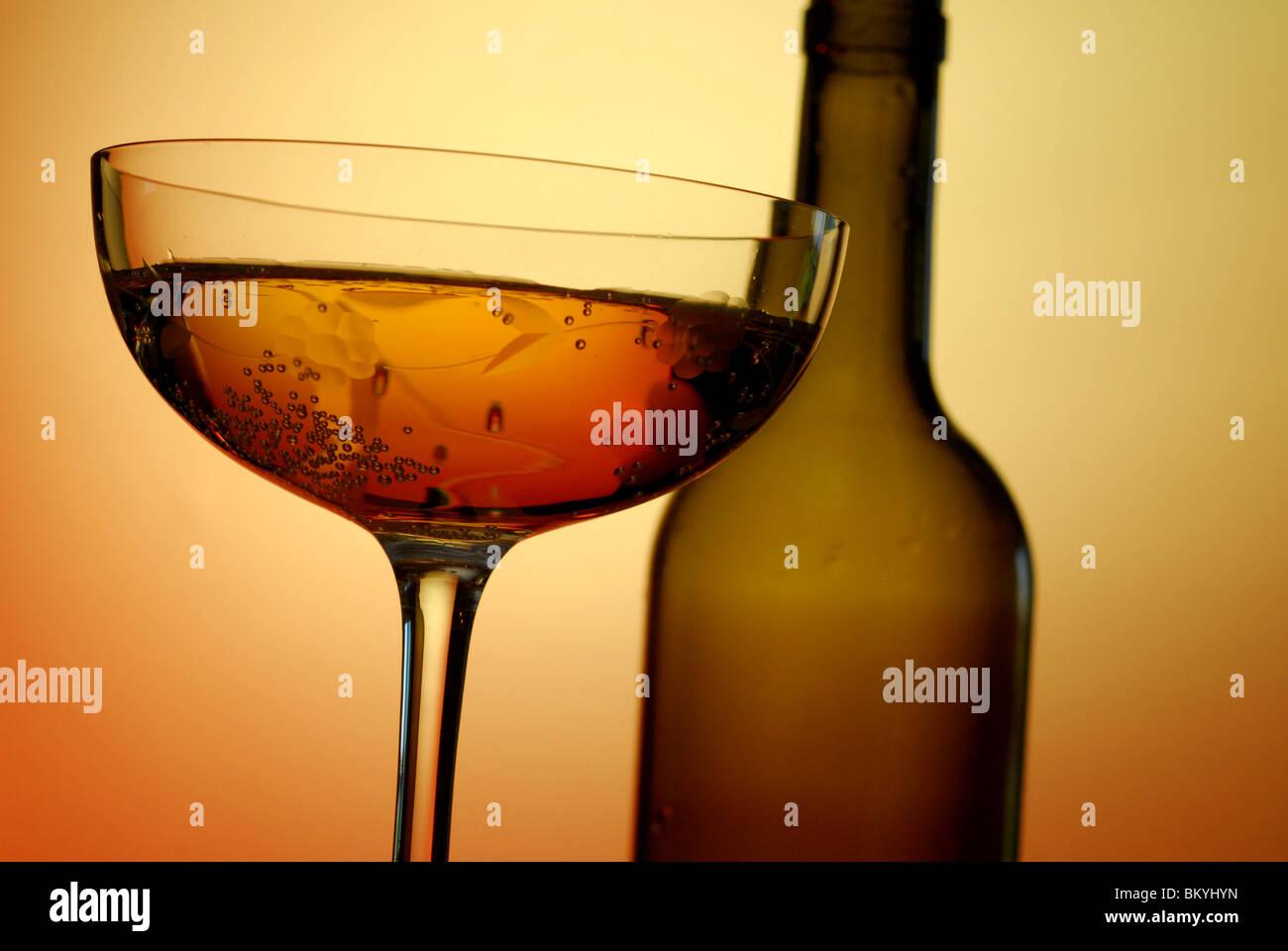Abstraktes Bild von einem Glas Wein von unten mit einer Flasche in der Ferne Stockbild