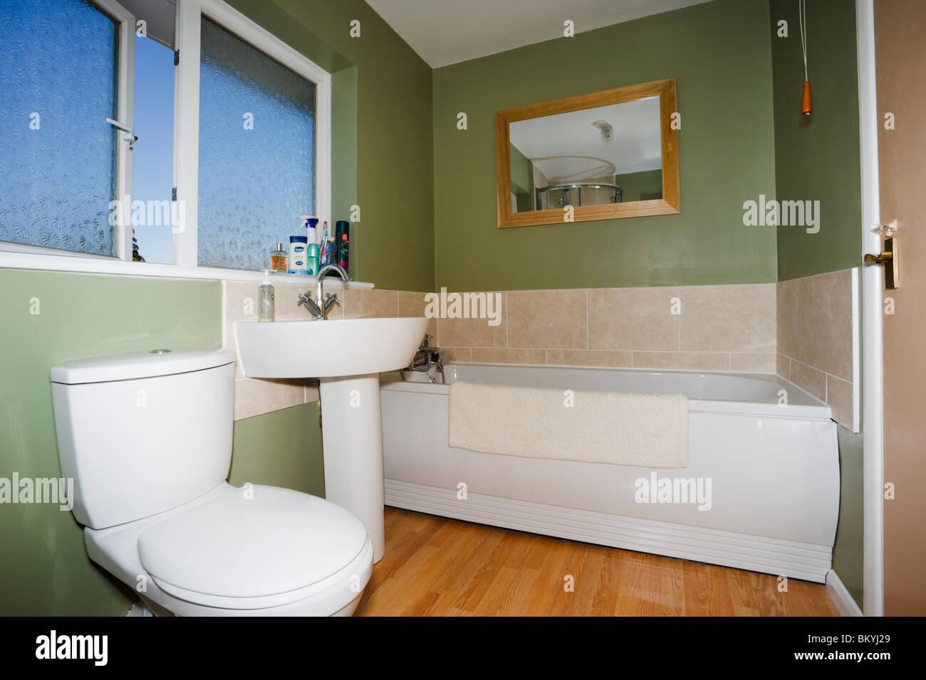 Bad Toilette mit grünen Wänden und weißen Suite mit Keramik Toilette, Waschbecken und Badewanne. Stockbild