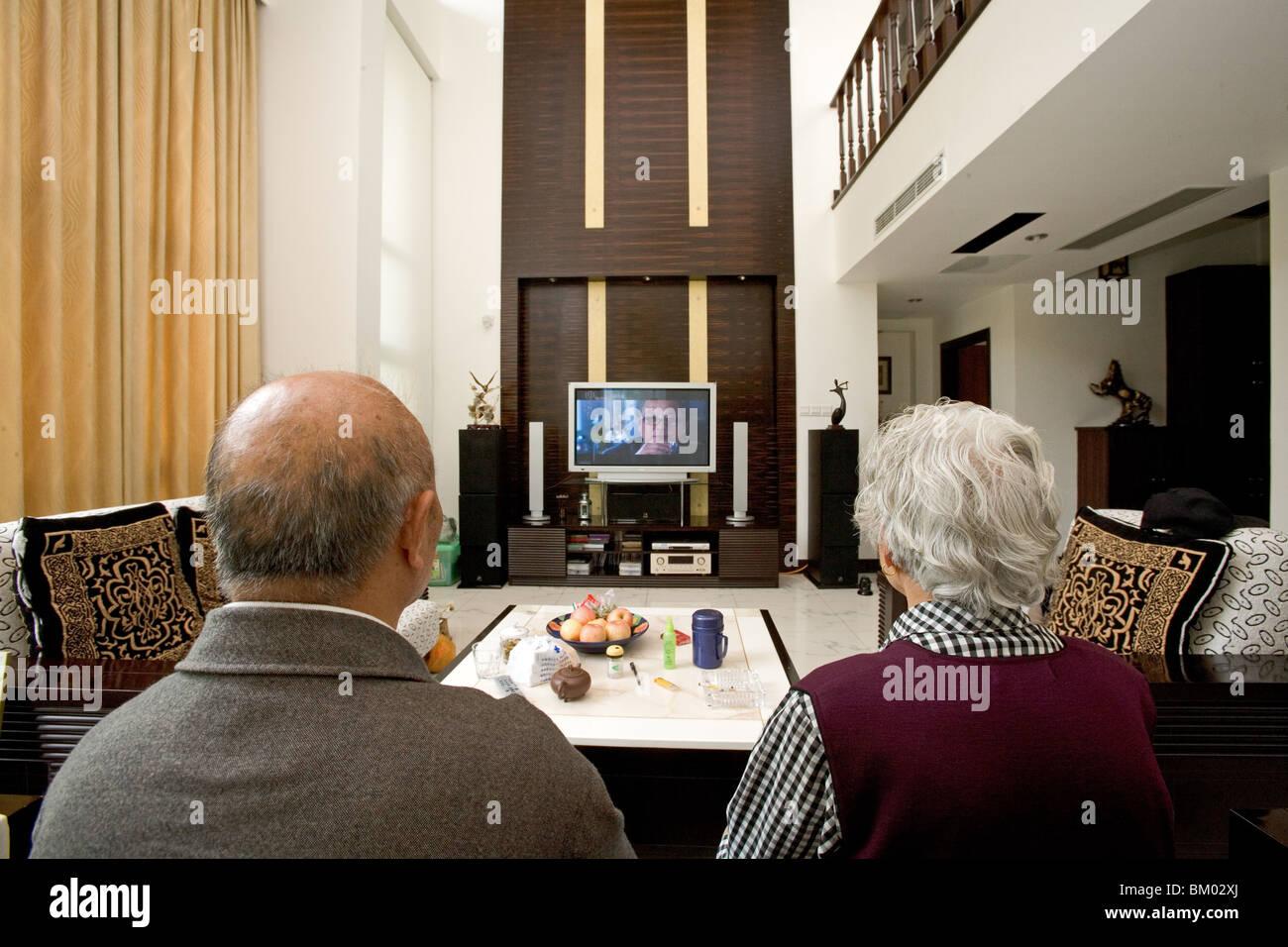 altes Ehepaar in moderne Villa, altes Ehepaar mit großen TV-Bildschirm, Wohnzimmer, Luxuswohnung, westlichen Stockbild