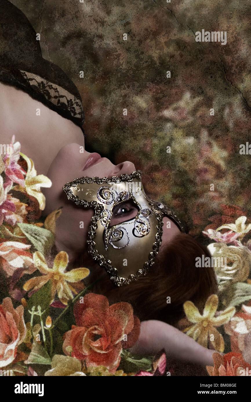 junge Frau wieder in einem Bett aus Blumen, liegen mit einer Partei-Maske Stockbild