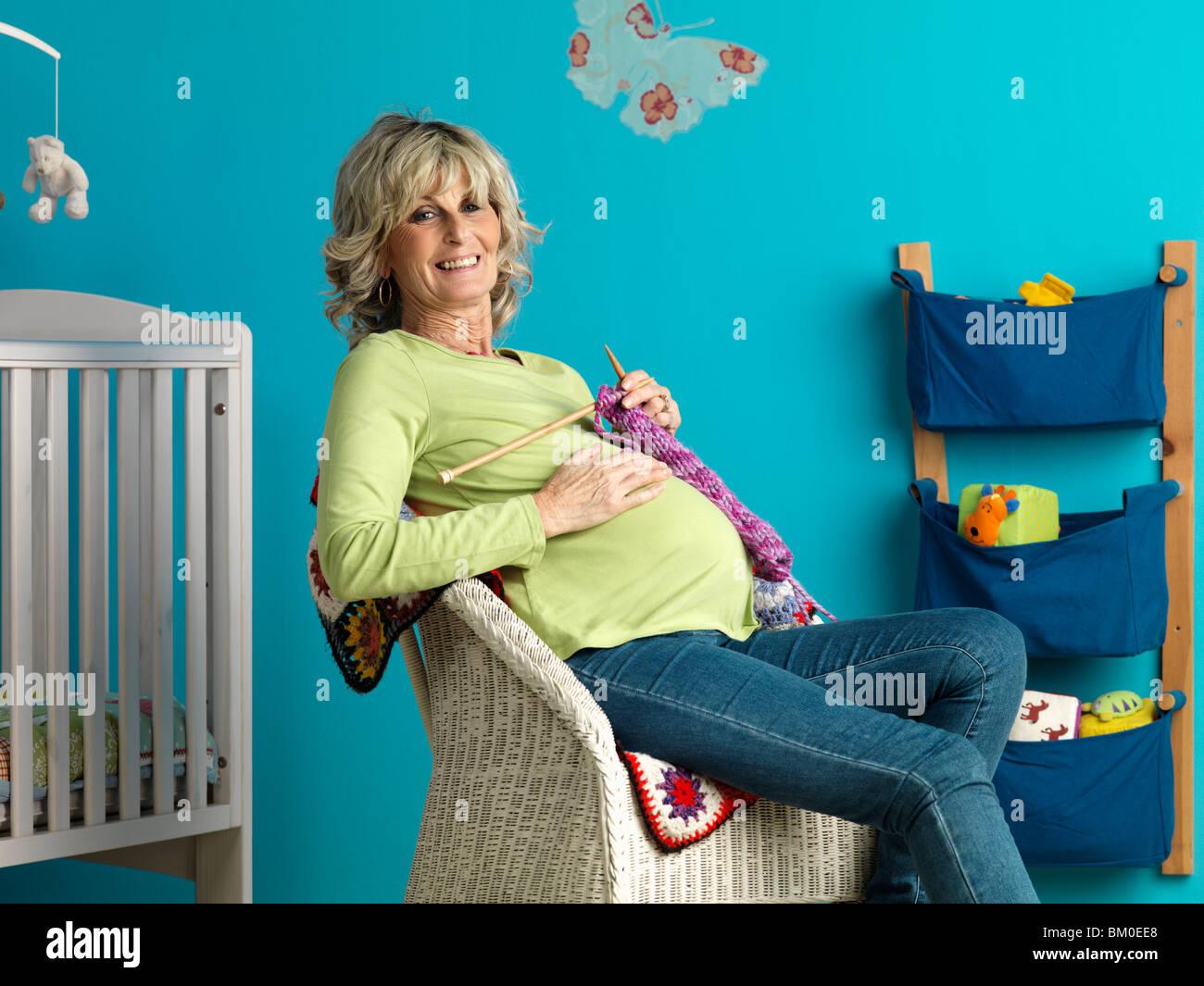 Schwangere Reife Frau stricken Stockbild