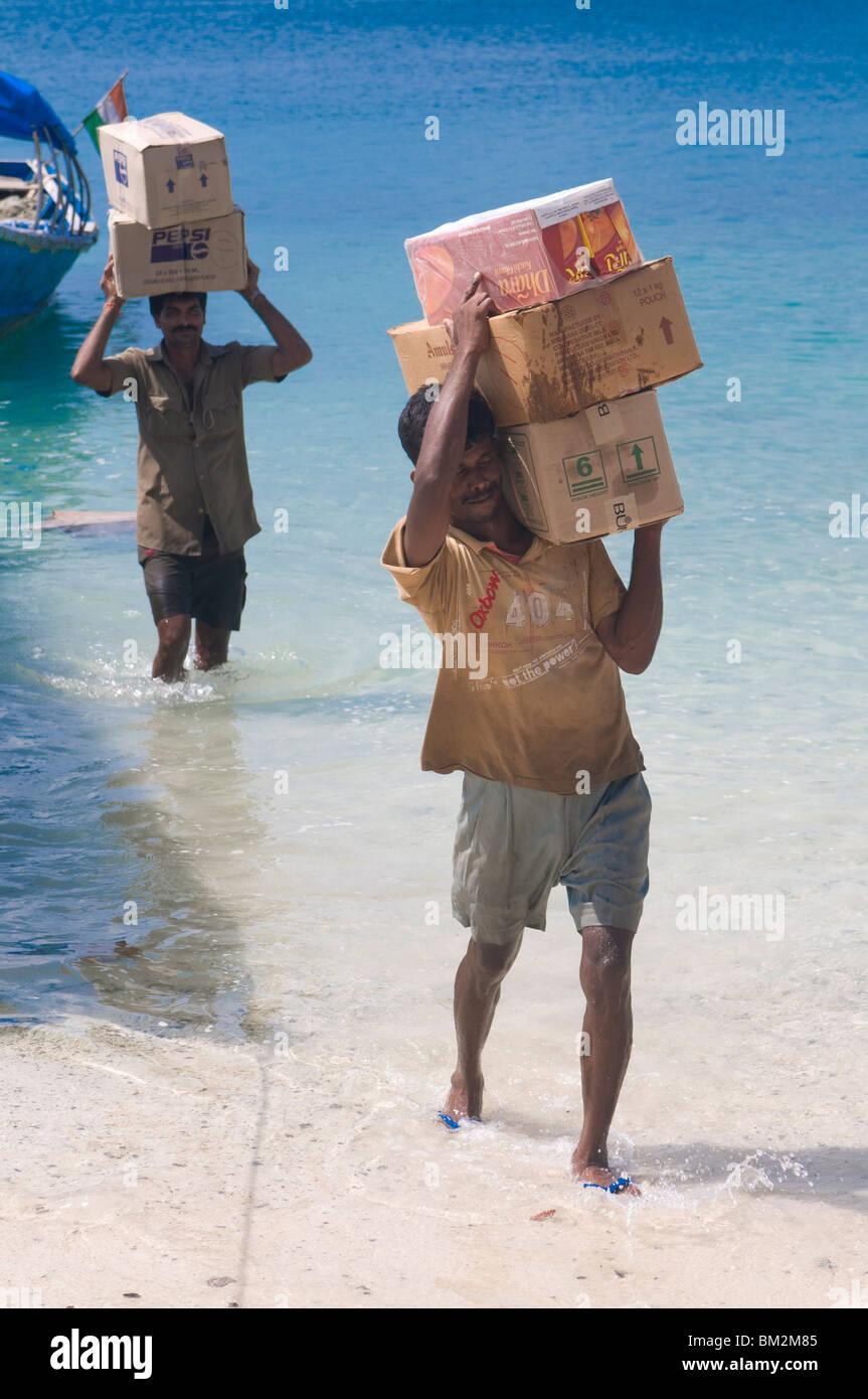 Träger, die Durchführung von riesiger Kisten von einem Boot aus Havelock Island, Andamanen, Indien, Indischer Stockbild