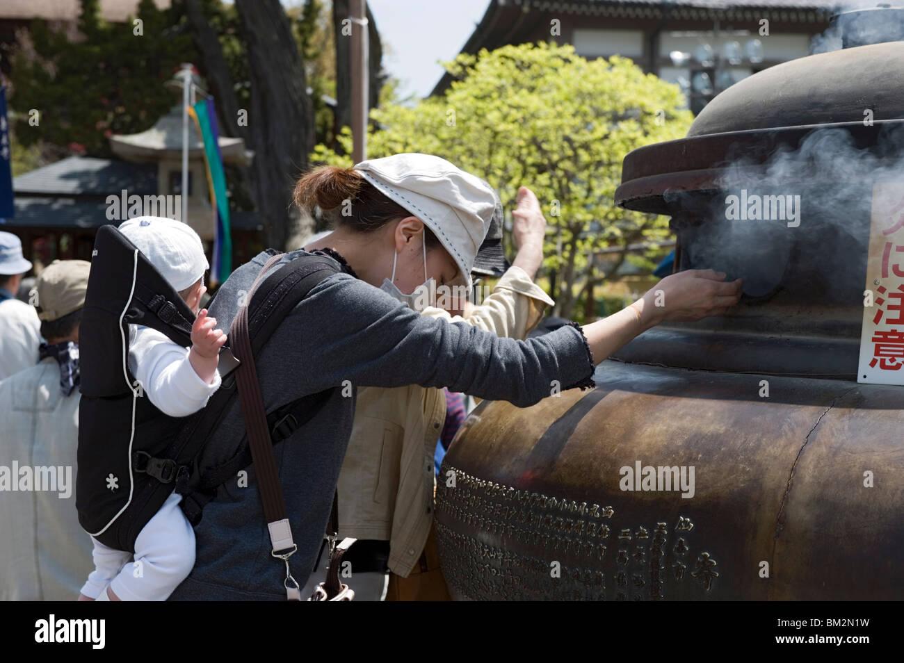 Mutter mit Baby mit Weihrauch Rauch zu heilen körperliche Beschwerden bei Zenkoji Tempel, Nagano-City, Japan Stockbild