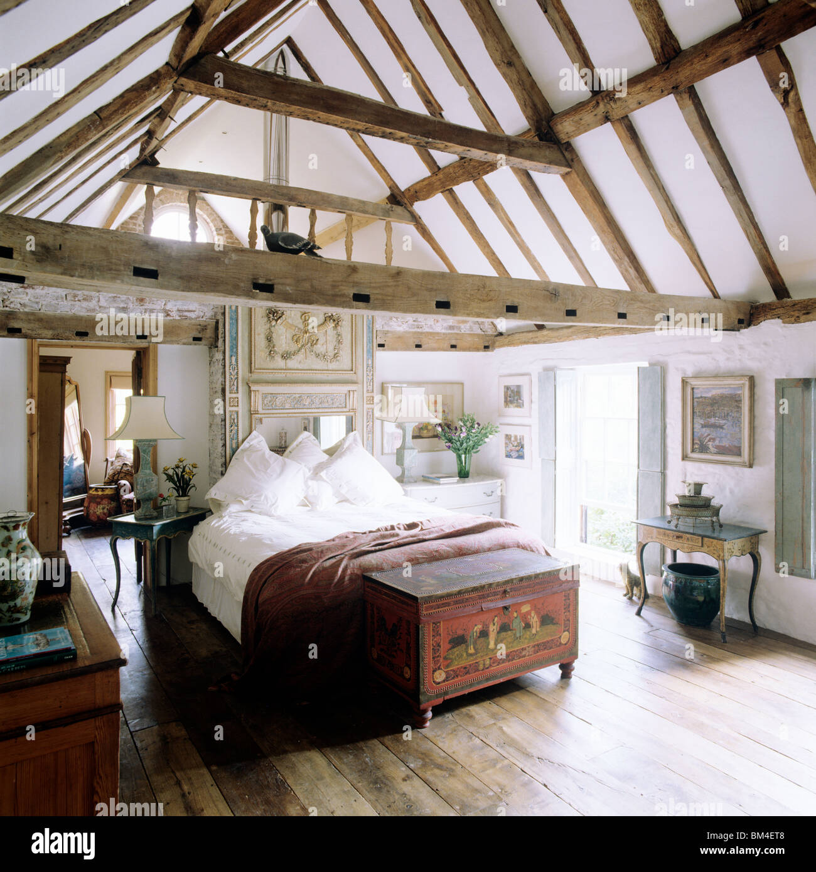 Land-Schlafzimmer mit Steildach decken und Balken mit Parkettboden ...
