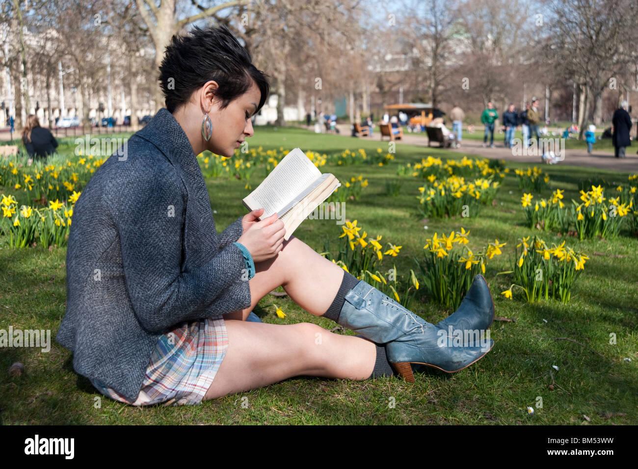 Junge Frau, die ein Buch in St James Park, London, England, UK Stockbild
