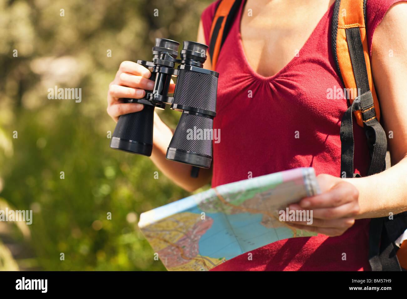 Blick auf weibliche Vogelbeobachter mit Fernglas und Karte zugeschnitten. Stockbild