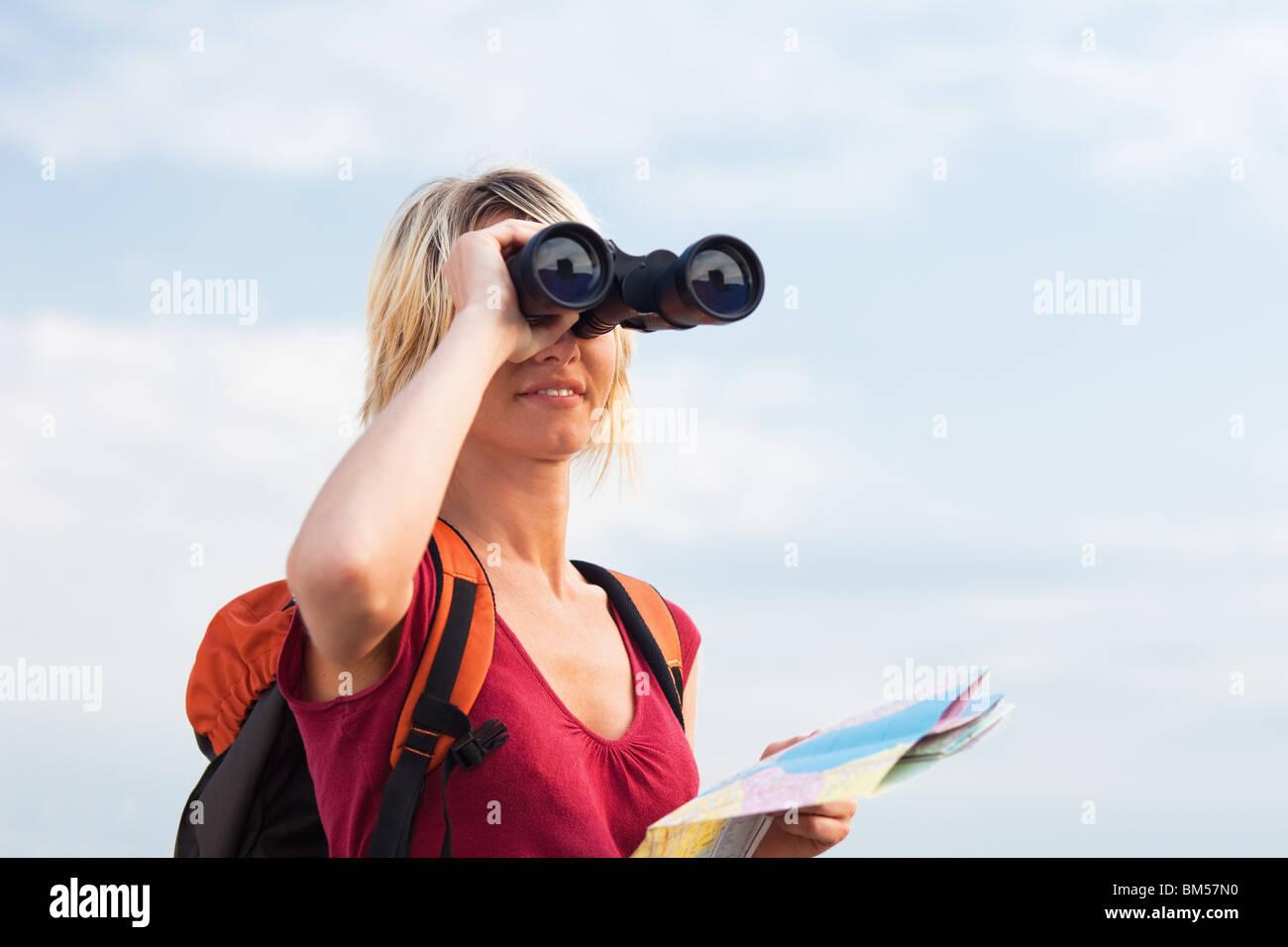 Blonde frau wandern und schauen durch ein fernglas stockfoto bild