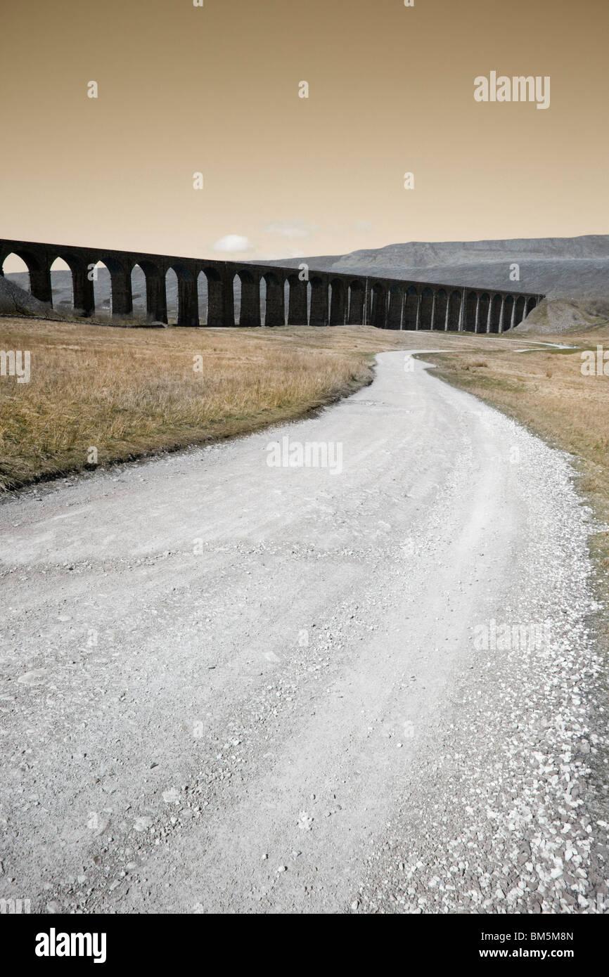 Eine lange Strecke zu einem dunklen ominösen Eisenbahnviadukt. Stockbild