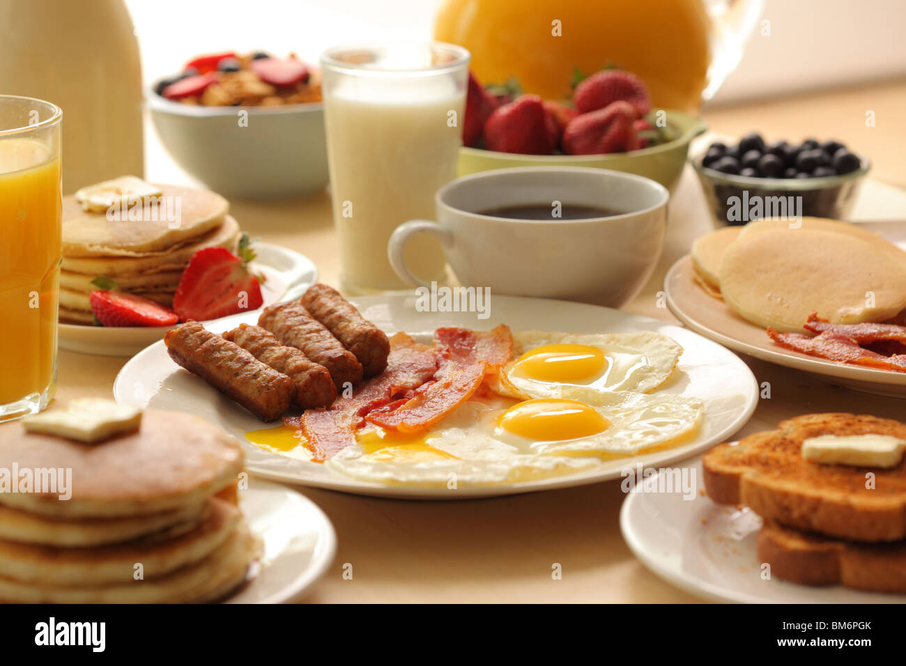 Frühstück, Wurst, Speck, Eiern, Toast, Kaffee, Müsli, Obst, Toast und Pfannkuchen Stockbild