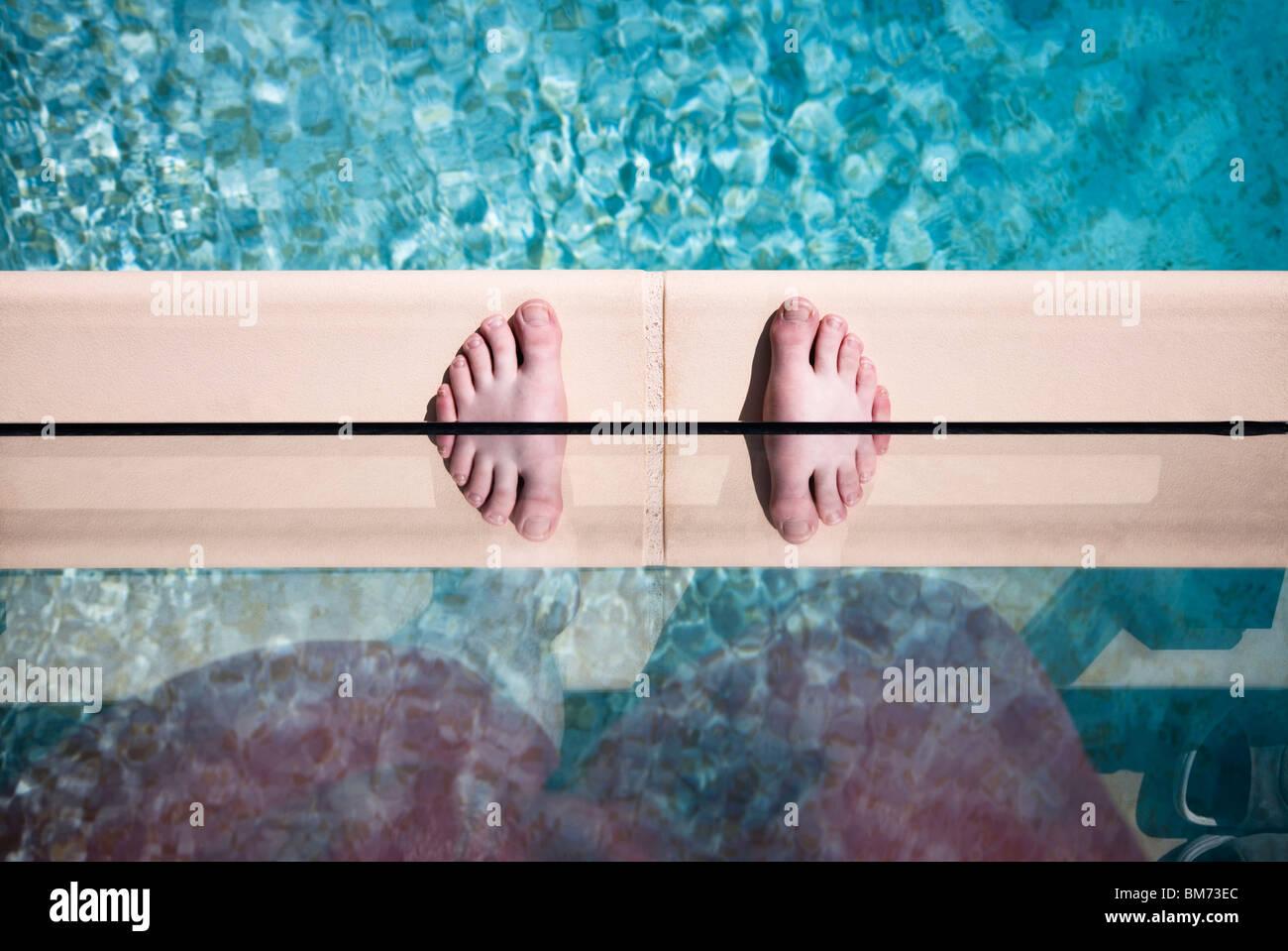 jemandes Füße am Rande eines Swimmingpools gegen Glas mit einer Reflexion Twin Füße Stockbild
