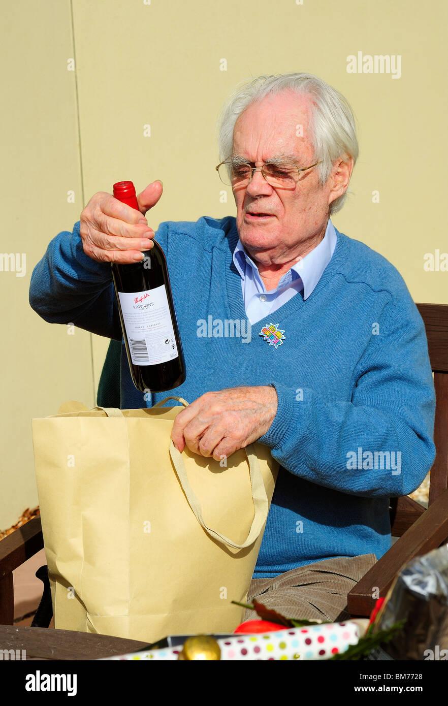 Ein Dankbarer Alterer Mann Nimmt Eine Flasche Weine Aus Einem Paket