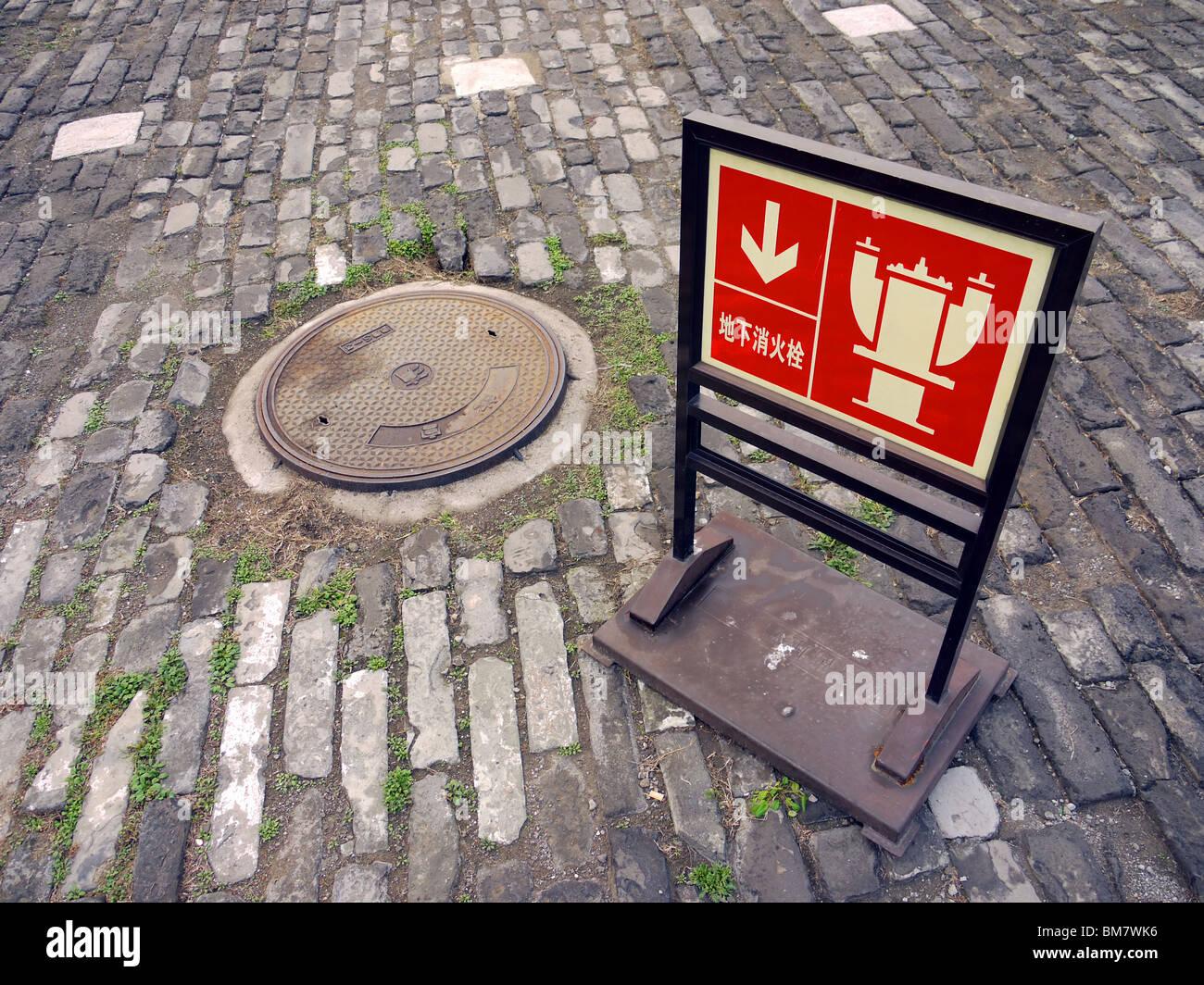 Rot anmelden chinesische deutete auf den Hydranten unter Kanal-Schacht auf dem Gebiet der verbotenen Stadt in Peking, Stockfoto