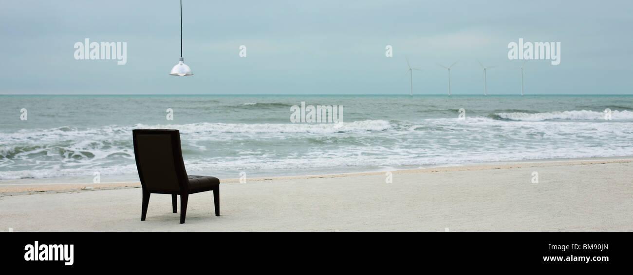 Lampe hängt über dem Stuhl am Strand, Windturbinen entlang Horizont sichtbar Stockbild