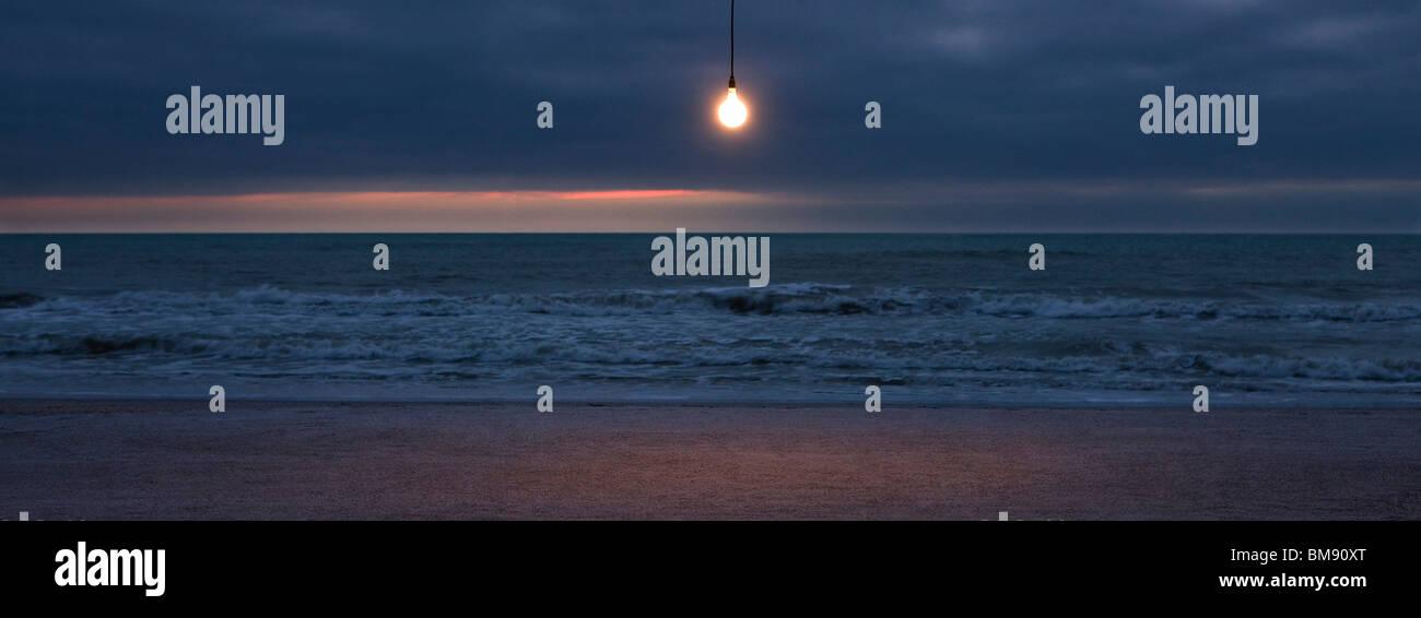 Glühbirne leuchtet über Strand bei Sonnenuntergang Stockbild