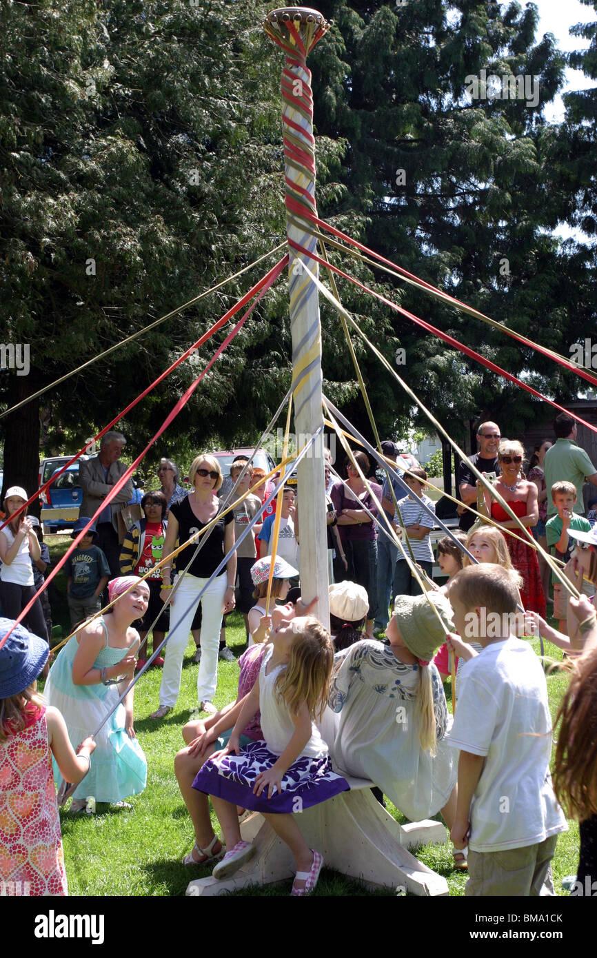Kinder tanzen den Maibaum auf einem Schulfest Sommer Stockbild